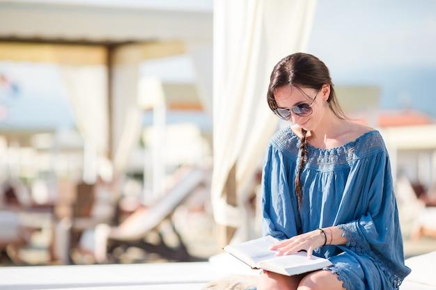 Menina da moda ler sentado em espreguiçadeiras brancas no weekeend praia europeia