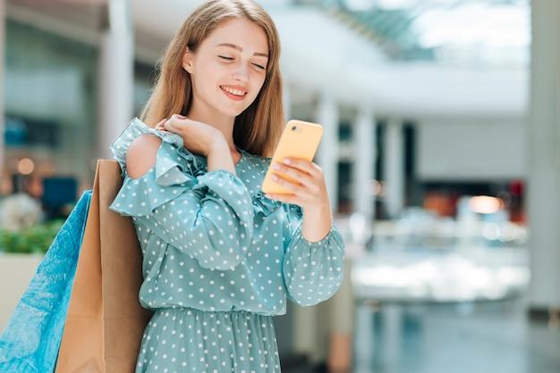 Menina da moda, verificando o telefone no shopping