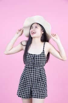 Menina da moda vestir-se com um gesto de mão em rosa