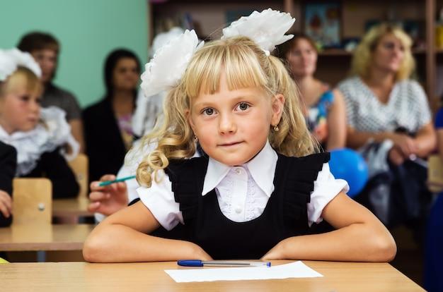 Menina da primeira série sentada em uma mesa na primeira aula do dia do conhecimento