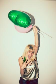 Menina dançando com balões e cerveja