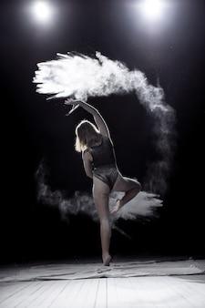 Menina dançando com uma farinha sobre o fundo preto sobre o céu
