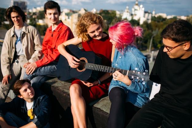 Menina dando aulas de violão para um amigo. tocando instrumento musical juntos. estilo de vida dos espíritos livres. lazer de adolescentes hippie urbanos em um telhado