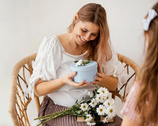 Menina dando flores da primavera e uma caixa de presente para a mãe