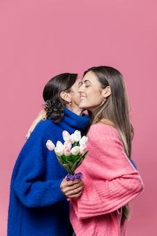 Menina dando flores para a mãe
