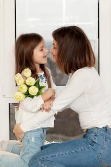 Menina dando flores para mãe
