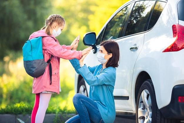 Menina dando high five para a mãe depois da escola perto do carro com máscaras médicas