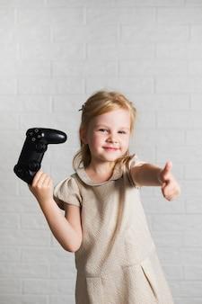 Menina dando sinal de ok para joystick