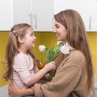 Menina dando tulipas brancas para mãe