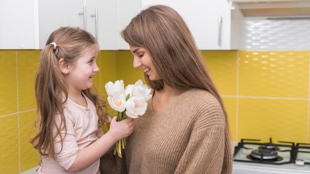 Menina dando tulipas para mãe
