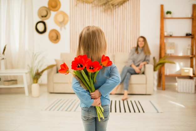 Menina dando tulipas vermelhas para a mãe na sala