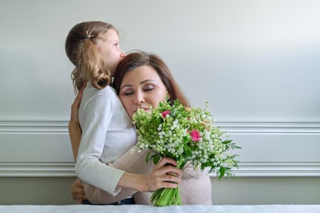 Menina dando um buquê para a mãe