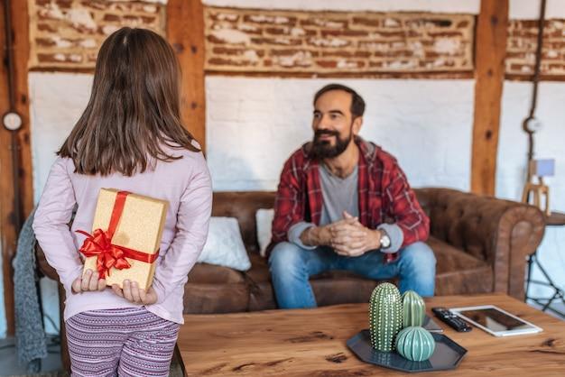 Menina dando um presente surpresa ó pai no sofá em casa no dia dos pais