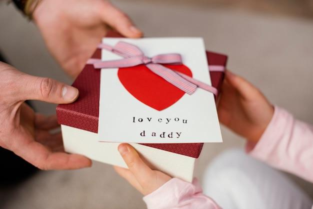 Menina dando uma caixa de presente para o pai no dia dos pais