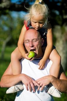 Menina dando uma maçã para o pai dela