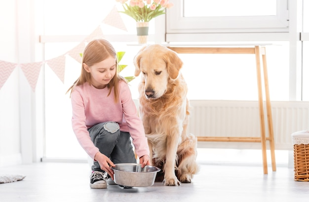 Menina dando uma tigela de metal para cachorro golden retriever fofo com ração na sala ensolarada de casa