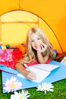 Menina das crianças que escreve o caderno na barraca de acampamento com flores