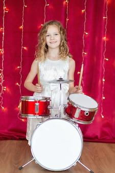 Menina de 10 anos toca bateria no vermelho com guirlandas de ano novo.
