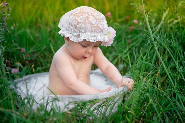 Menina de 10 meses de idade toma banho em uma bacia na grama no verão.