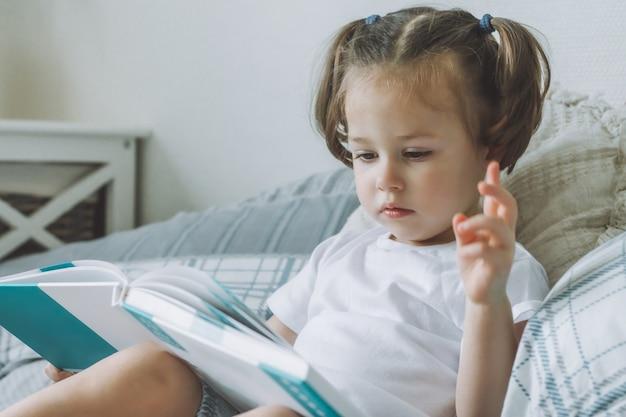 Menina de 2 a 4 anos de cabelos escuros com dois rabos de cavalo sentada na cama com travesseiros e lendo um livro