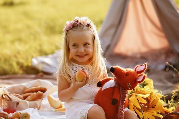 Menina de 3 anos comendo pêssego no verão em um piquenique