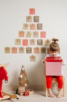 Menina de 3 anos de idade da criança sentada perto do calendário do advento artesanal de natal e abrindo a caixa de presente no quarto das crianças.