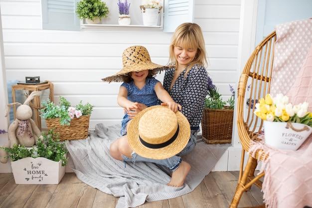 Menina de 4 a 5 anos brincando com chapéus de palha na varanda de casa com a mãe nos braços. riso, felicidade, alegria, conceito de maternidade
