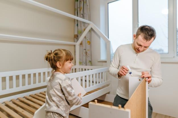 Menina de 4 anos ajuda o pai a montar ou consertar a gaveta da cama do quarto dos filhos.