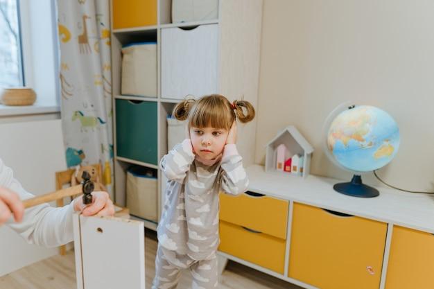 Menina de 4 anos fecha os ouvidos com as mãos por causa do barulho enquanto seu pai usa o martelo para consertar a gaveta da cama no quarto das crianças.