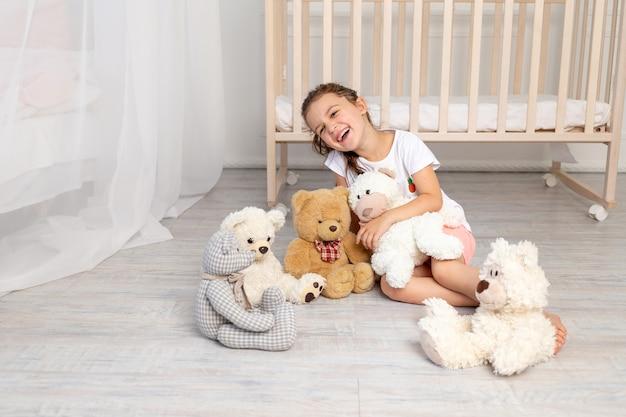 Menina de 5 a 6 anos brincando no quarto das crianças com ursinhos de pelúcia