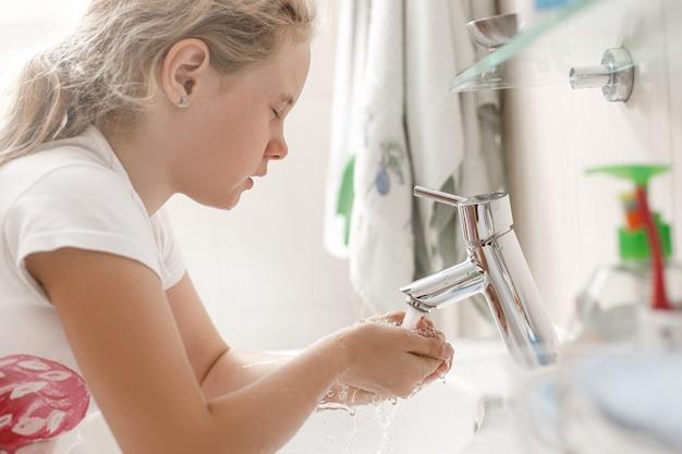 Menina de 8 anos lava o rosto no banheiro pela manhã.
