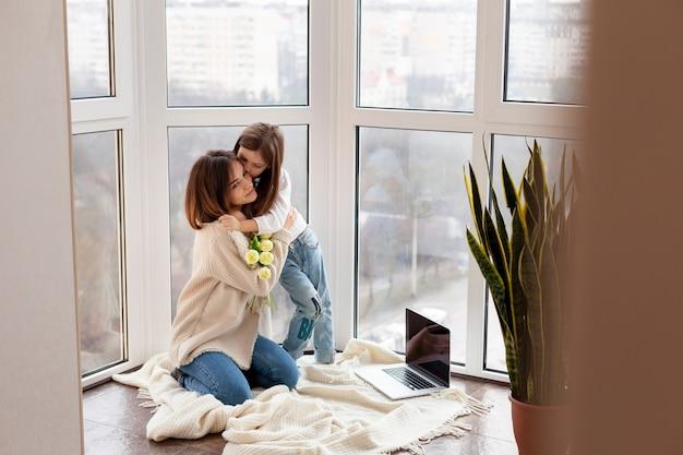 Menina de alto ângulo, abraçando a mãe