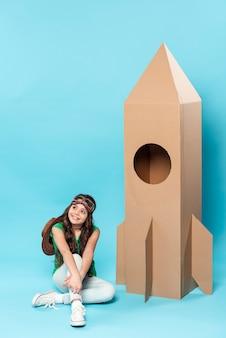 Menina de alto ângulo com brinquedo de avião dos desenhos animados