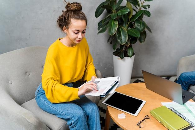 Menina de alto ângulo com notebook dentro de casa