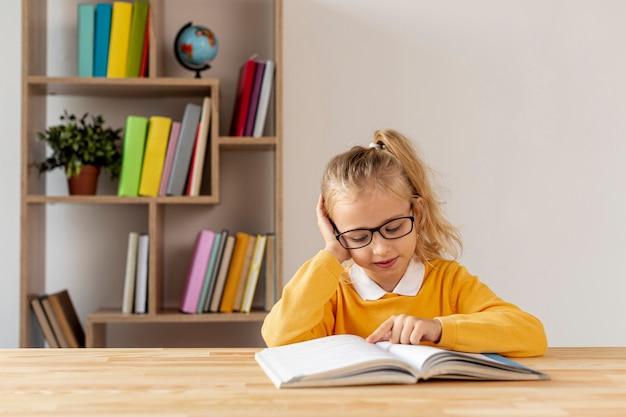 Menina de alto ângulo com óculos lendo