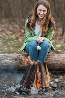 Menina de alto ângulo, cozinhar marshmallow
