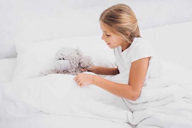 Menina de alto ângulo, ficar na cama com seu ursinho de pelúcia
