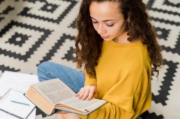 Menina de alto ângulo, lendo um livro dentro de casa