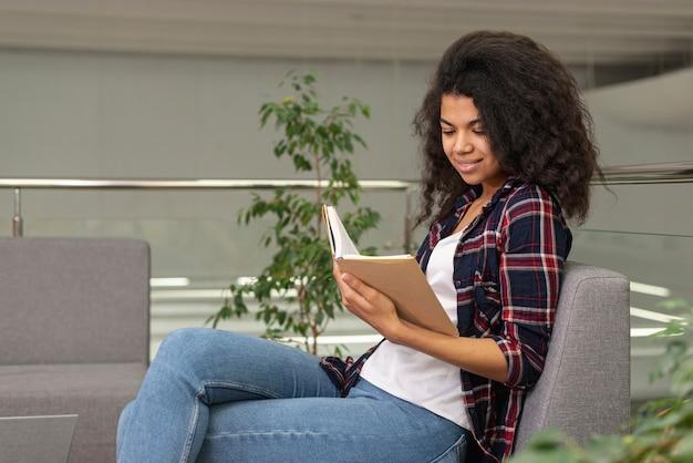 Menina de alto ângulo na leitura da poltrona