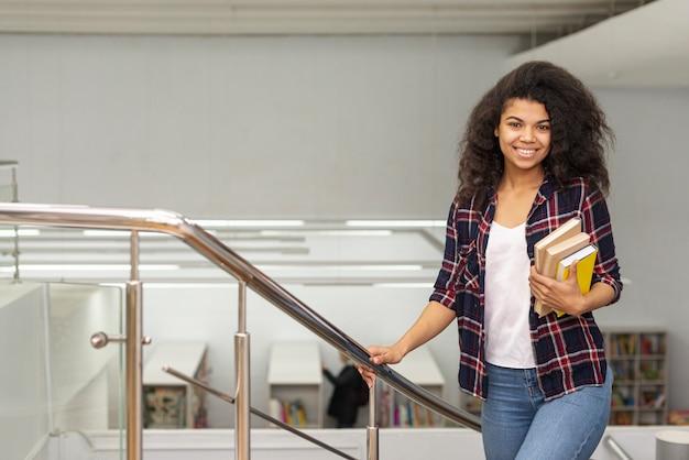 Menina de alto ângulo nas escadas com pilha de livros
