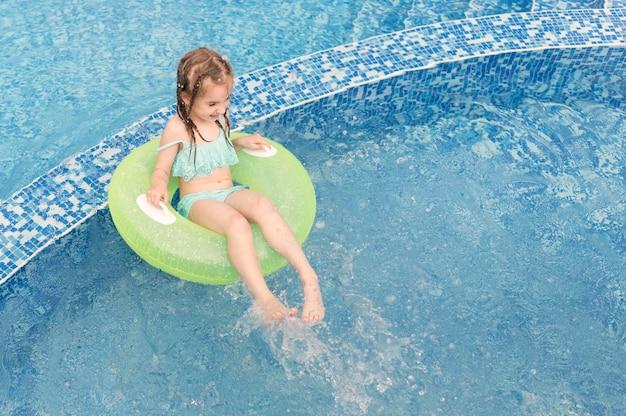 Menina de alto ângulo no flutuador de piscina