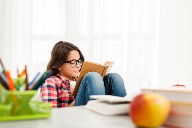 Menina de ângulo alto em casa lendo