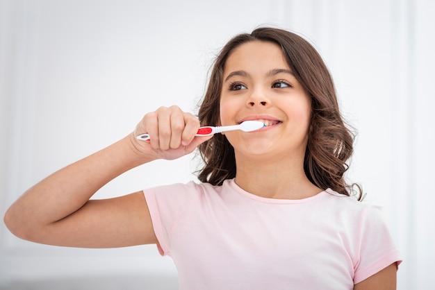 Menina de ângulo baixo bonito escovando theets