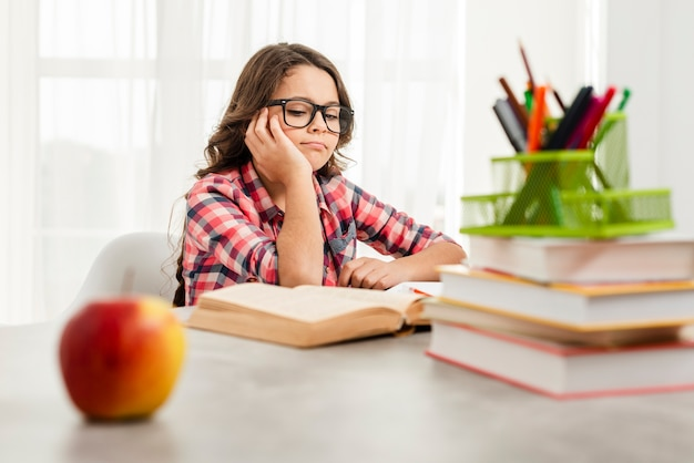 Menina de ângulo baixo com óculos estudando