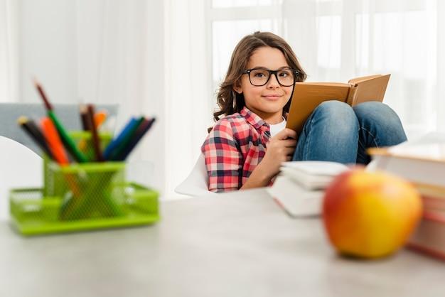 Menina de ângulo baixo em casa lendo