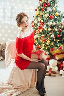 Menina de ano novo com um presente nas mãos perto da árvore de natal
