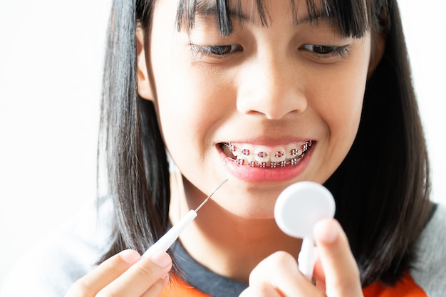 Menina de aparelho dental sorrindo e limpando os dentes, ela se sente feliz e tem boa atitude com dentista