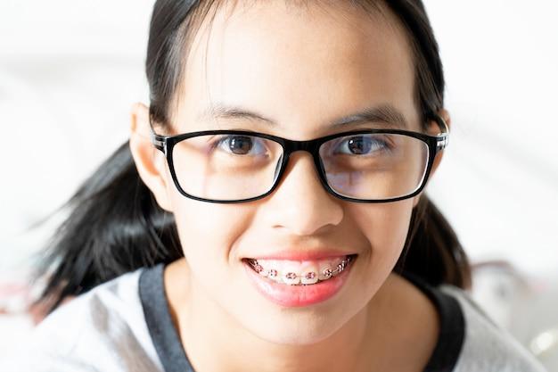 Menina de aparelho dental sorrindo e olhando para a câmera, ela se sente feliz e tem boa atitude com dentista