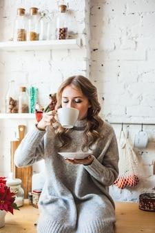 Menina de aparência europeia, sentada na cozinha, bebendo chá ou café em uma caneca branca