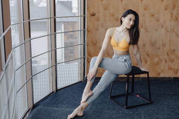 Menina de aptidão atraente jovem sentado na cadeira perto da janela no fundo de uma parede de madeira